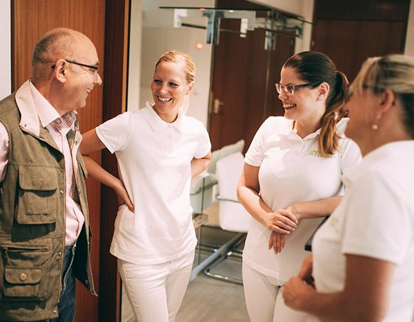 Drei Zahnmedizinische Fachangestellte unterhalten sich herzlich mit einem älteren Patienten im Flur der Zahnarztpraxis Dr. Pfitzer in Stuttgart