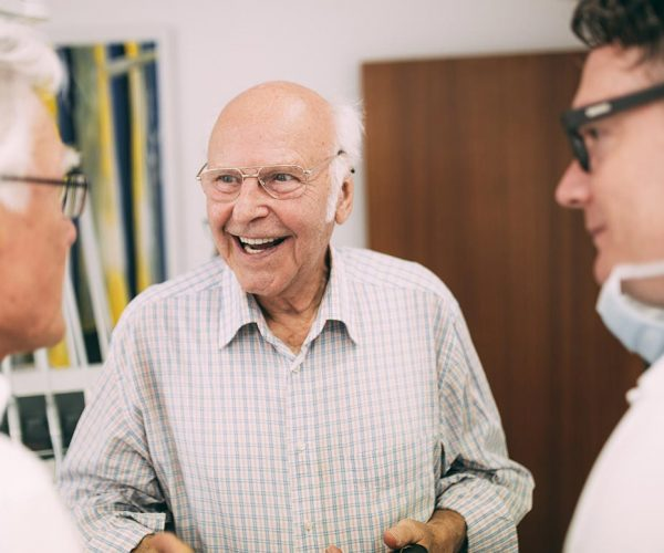 Gesundes Lächeln eines älteren Herren: Das ist der Anspruch von Zahnarzt Dr. med. dent. Hanns Joachim Pfitzer, der neben ihm in seiner Zahnarztpraxis in Stuttgart steht