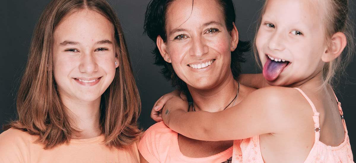 Eine Patientin lacht zusammen mit ihren Kindern, eines hat eine blau angefärbte Zunge, bei Ihrem Zahnarzt Besuch in der Zahnarztpraxis Dr. Pfitzer in Stuttgart