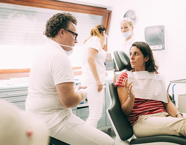 Zahnarzt Dr. med. dent. Hanns Joachim Pfitzer erklärt zusammen mit seinen Mitarbeiterinnen im Hintergrund einer Patientin im Behandlungsstuhl wie Zahnersatz und Inlays in einer Sitzung in der Zahnarztpraxis Dr. Pfitzer in Stuttgart hergestellt werden