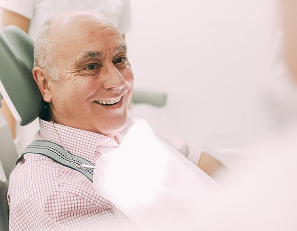 Ein älterer Patient freut sich über das Gefühl natürlicher Zähne bei künstlichen Implantaten aus der Zahnarztpraxis Dr. Pfitzer in Stuttgart