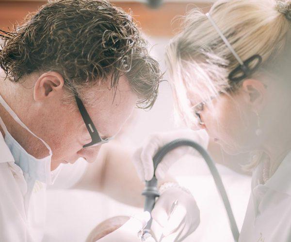 Zahnarzt Dr. med. dent. Hanns Joachim Pfitzer und eine Assistentin bei einer Versorgung mit Zahnimplantaten – für feste Zähne aus der Zahnarztpraxis Dr. Pfitzer in Stuttgart