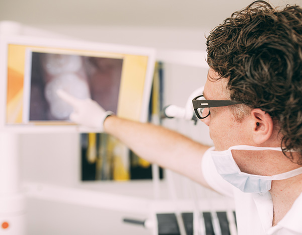 Zahnarzt Dr. med. dent. Hanns Joachim Pfitzer zeigt mit seinem Finger auf eine Monitoraufnahme, die weiter im Hintergrund liegt. Dort zu sehen: natürlicher Zahnersatz aus der Zahnarztpraxis in Stuttgart