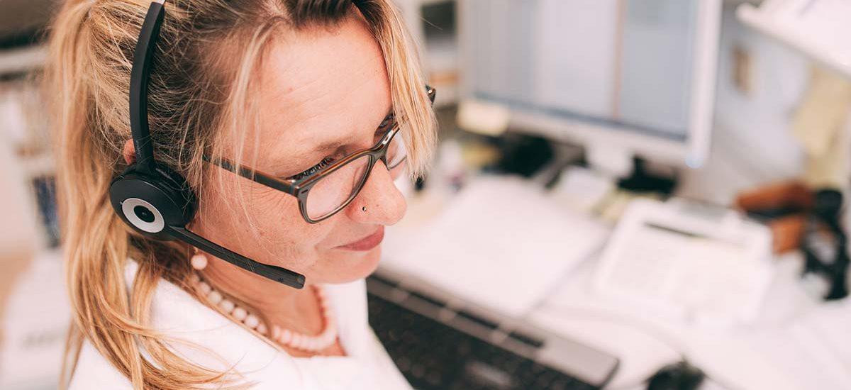 Eine Mitarbeiterin mit Headset sitzt an der Rezeption und ist im ständigen Austausch: mit Patienten, für Neuigkeiten, Jobs und Themen der Zahnmedizin in der Zahnarztpraxis Dr. Pfitzer in Stuttgart