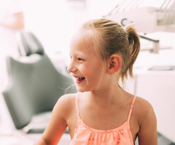 Ein kleines Mädchen lacht herzlich während ihres Besuchs beim Kinderzahnarzt Dr. med. dent. Hanns Joachim Pfitzer in der Zahnarztpraxis in Stuttgart