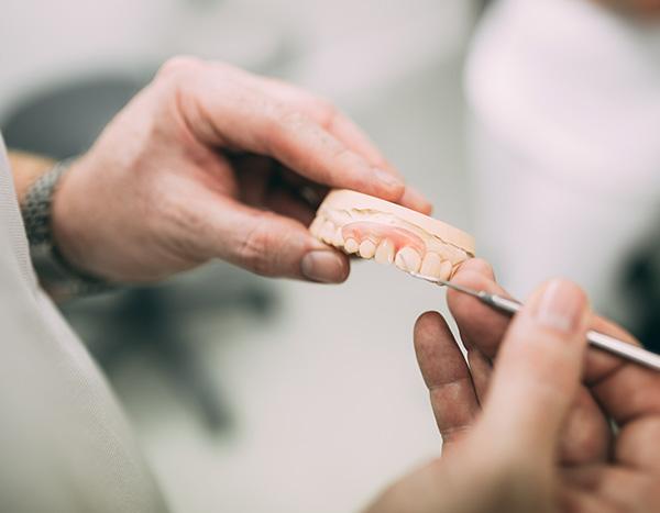 Zahnarzt Dr. med. dent. Hanns Joachim Pfitzer zeigt anhand einer Prothese den individuellen Zahnersatz aus Deutschland, der bei guter Vorsorge auch von Krankenkassen bezuschusst wird