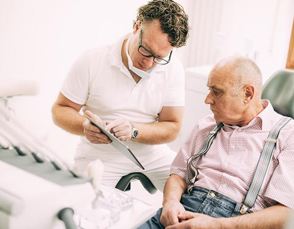 Zahnarzt Dr. med. dent. Hanns Joachim Pfitzer zeigt in seiner Zahnarztpraxis in Stuttgart einem älteren Patienten mit einem Pad die Ursachen und den Verlauf der Zahnfleischerkrankung Parodontitis