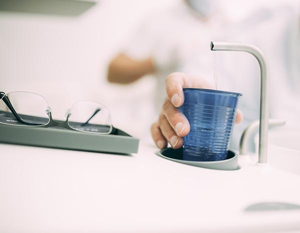 Detailaufnahme einer Hand, die zum Mundspülbecher greift – der Abschluss für ein sauberes und frisches Mundgefühl nach einer professionellen Zahnreinigung in der Zahnarztpraxis Dr. Pfitzer in Stuttgart