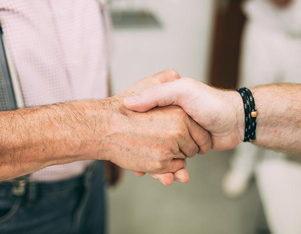 Detailaufnahme des Händeschüttelns von Zahnarzt Dr. med. dent. Hanns Joachim Pfitzer und einem Patienten nach einer erfolgreichen professionellen Zahnreinigung in der Zahnarztpraxis Dr. Pfitzer in Stuttgart