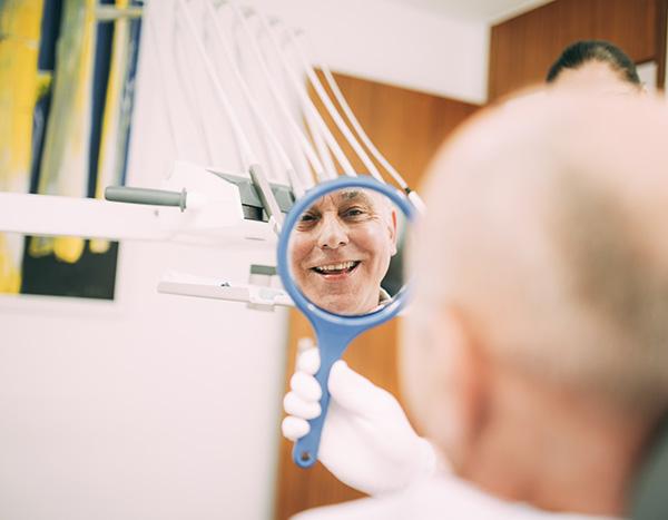 Eine Mitarbeiterin der Zahnarztpraxis Dr. Pfitzer in Stuttgart zeigt einem Patienten das Ergebnis seiner Prophylaxe Behandlung mithilfe eines kleinen Spiegels