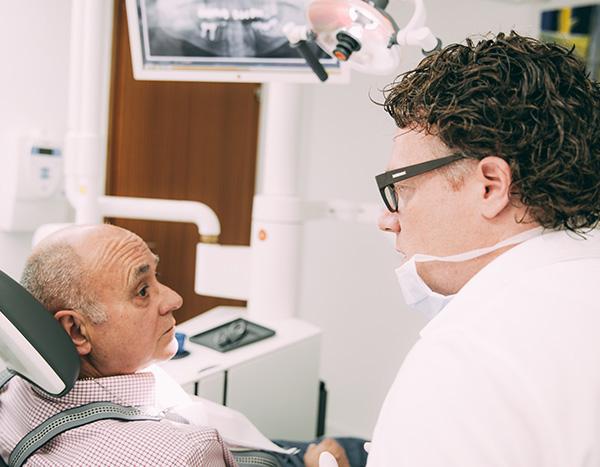 Zahnarzt Dr. med. dent. Hanns Joachim Pfitzer klärt einen älteren Patienten auf dem Behandlungsstuhl seiner Zahnarztpraxis in Stuttgart auf