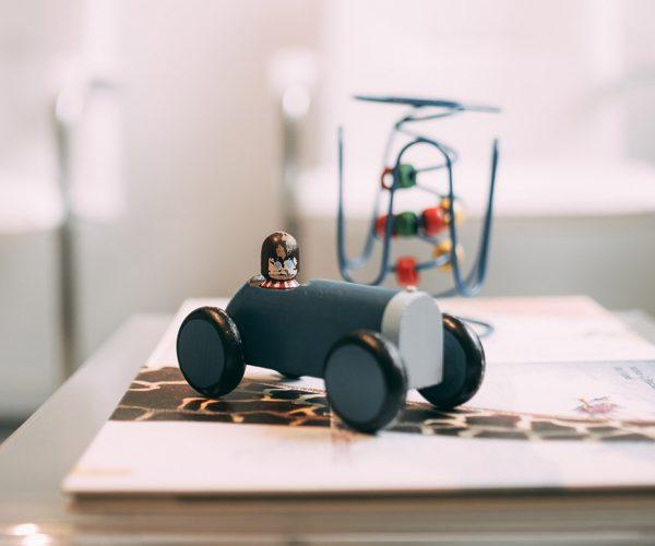 Die Detailaufnahme eines Holz-Spielzeugautos im Wartebereich der Zahnarztpraxis Dr. Pfitzer symbolisiert die schnelle Verkehrsanbindung für Patienten aus Stuttgart, Stuttgart-Heumaden oder Stuttgart-Sillenbuch