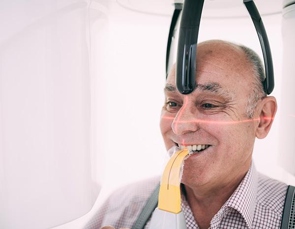 Ein Patient steht während der Aufnahmen des digitalen Röntgens im Digitalen Volumentomografen der Zahnarztpraxis Dr. Pfitzer in Stuttgart und wird digital gescannt