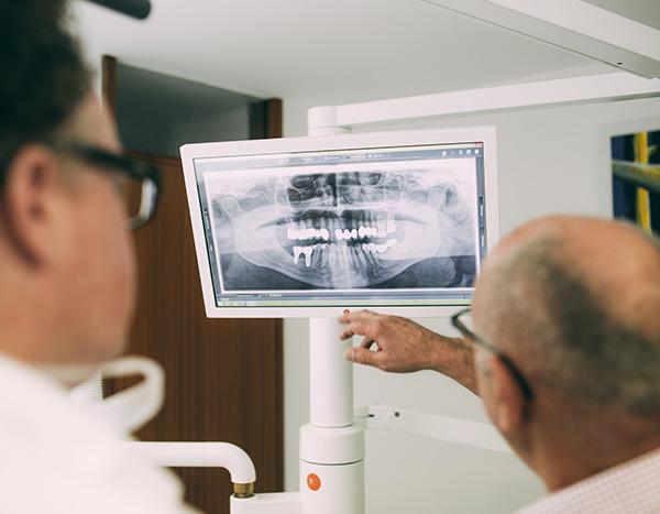 Zahnarzt Dr. med. dent. Hanns Joachim Pfitzer zeigt einem älteren Patienten eine Röntgenaufnahme – und das direkt vom Behandlungsstuhl der Zahnarztpraxis Dr. Pfitzer in Stuttgart aus