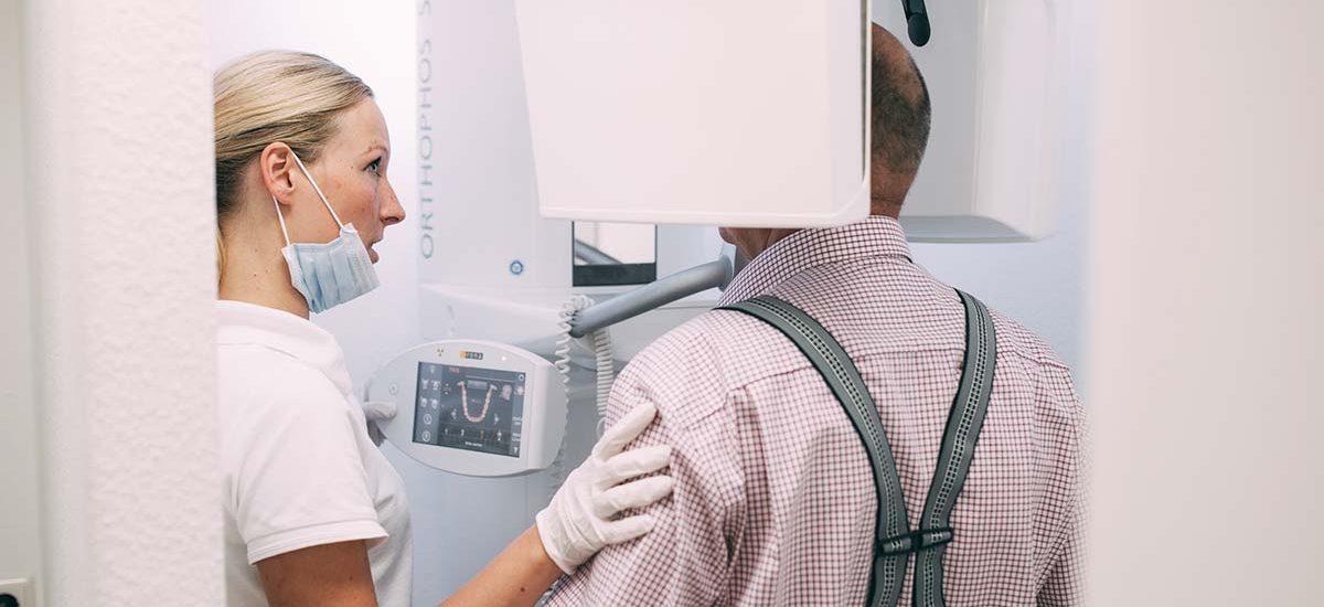 Ein Patient steht im digitalen Volumentomografen (DVT) der Zahnarztpraxis Dr. Pfitzer in Stuttgart. Eine Mitarbeiterin leitet ihn bei der digitalen Diagnostik an