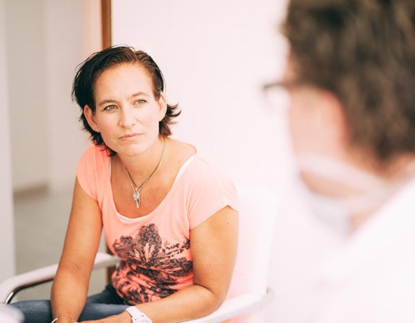 Eine Patientin in rotem Shirt lauscht gespannt der Beratung zu Veneers von Ihrem Zahnarzt Dr. med. dent. Hanns Joachim Pfitzer in der Zahnarztpraxis in Stuttgart