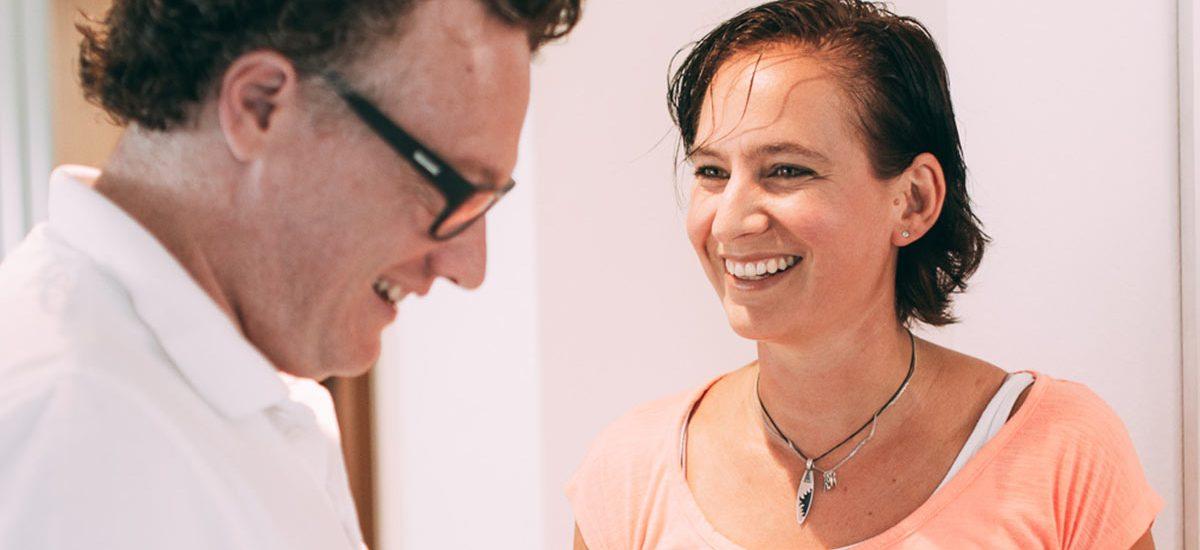 Eine Patientin mit einem strahlenden Lächeln freut sich gemeinsam mit ihrem Zahnarzt Dr. med. dent. Hanns Joachim Pfitzer über die erfolgreiche Behandlung mit Veneers in der Zahnarztpraxis Dr. Pfitzer in Stuttgart