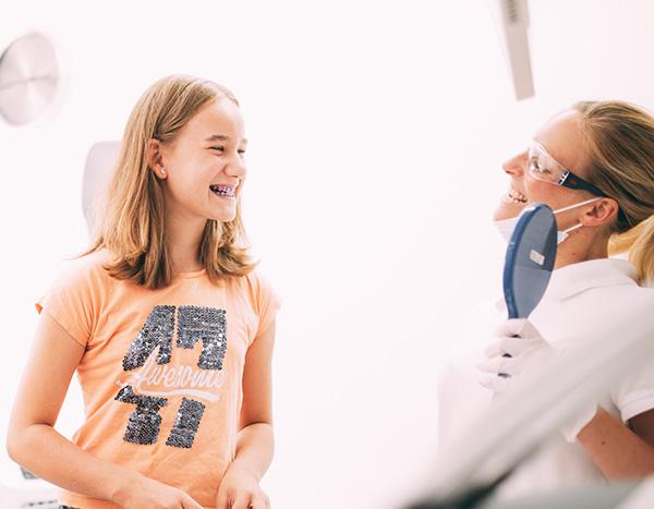 Ein junges Mädchen mit blau angefärbten Zähnen schneidet ganz stressfrei zusammen mit einer Mitarbeiterin der Zahnarztpraxis Dr. Pfitzer in Stuttgart Grimassen