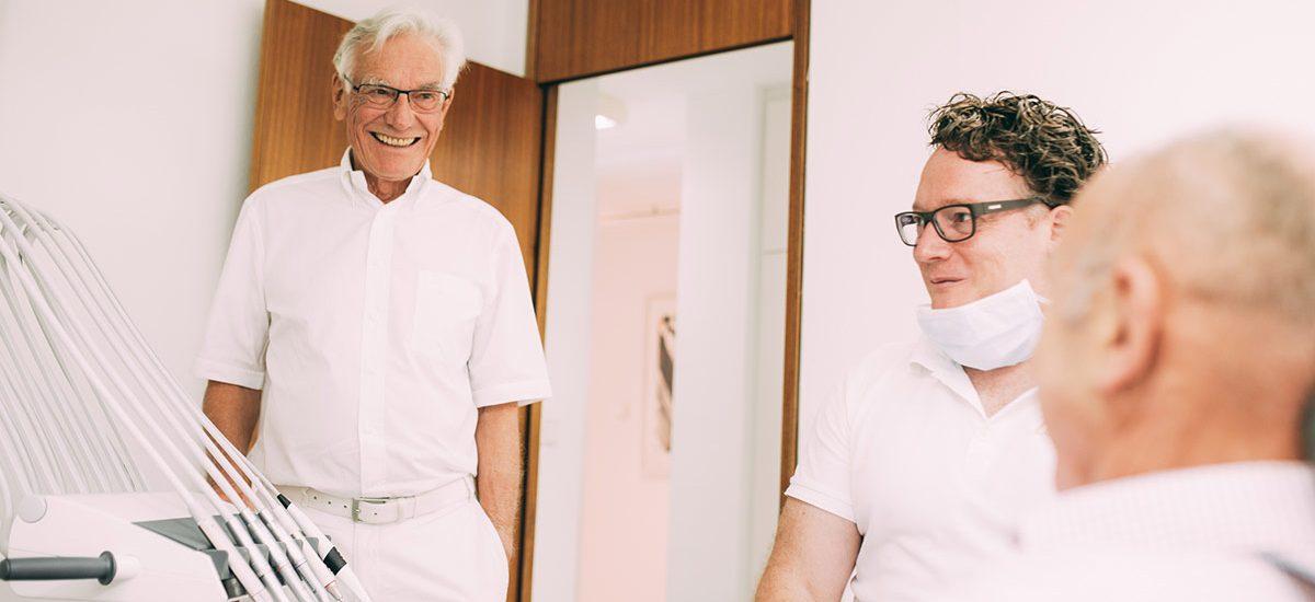 Zahnarzt Dr. med. dent. Hanns Joachim Pfitzer und sein Vater Dr. med. dent. Hans in einem vertrauensvollen Gespräch mit einem Patienten der Zahnarztpraxis Dr. Pfitzer in Stuttgart