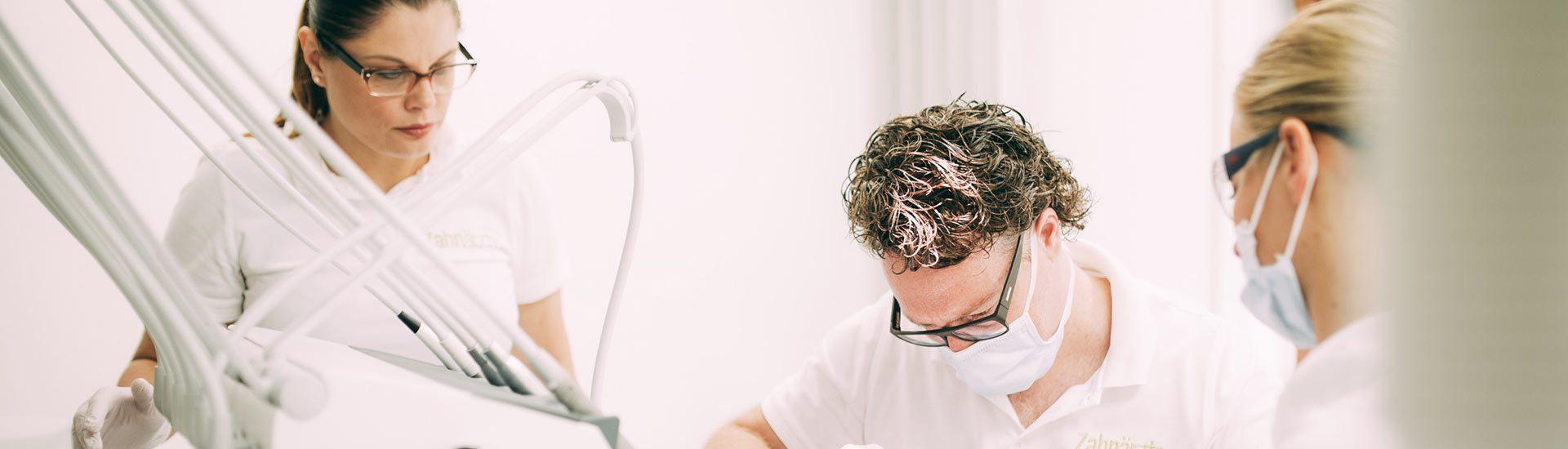 Zahnarzt Dr. med. dent. Hanns Joachim Pfitzer behandelt gemeinsam mit zwei Assistentinnen einen Patienten für eine bessere Mundgesundheit und eine neue Lebensqualität