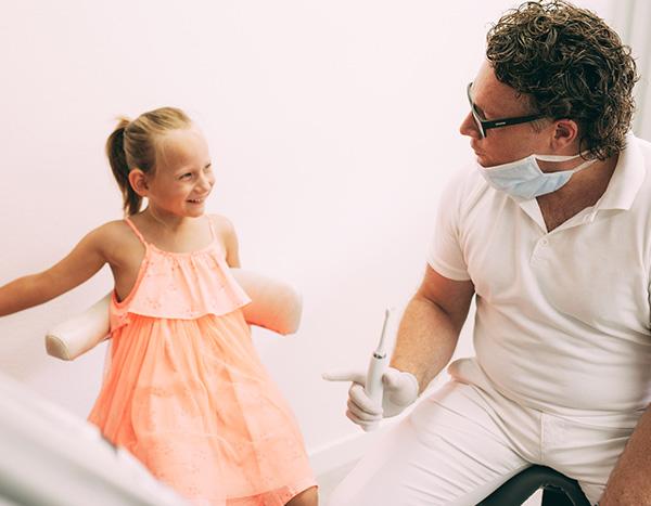 Dr. med. dent. Hanns Joachim Pfitzer erklärt einer kleiner jungen Patienten im Behandungszimmer seiner Zahnarztpraxis in Stuttgart-Heumaden mit einer elektrischen Zahnbürste und viel Geduld, wie angstfrei ein Zahnarzt-Besuch sein kann
