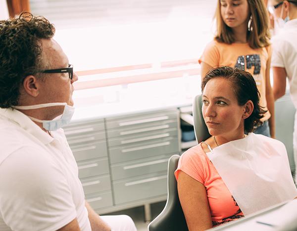 Dr. med. dent. Hanns Joachim Pfitzer klärt in seiner Zahnarztpraxis in Stuttgart eine Patientin über die Maßnahmen nach einem Zahnunfall auf