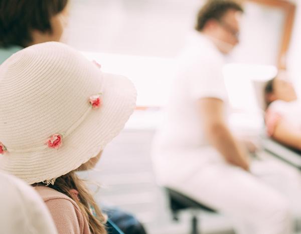 Eine junge Patientin mit sommerlichen Hut beobachtet ihre Mutter und Dr. med. dent. Hanns Joachim Pfitzer beim Zahn-Check in der Zahnarztpraxis Dr. Pfitzer in Stuttgart vor dem gemeinsamen Urlaub