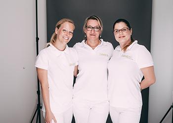 Drei Mitarbeiterinnen der Zahnarztpraxis Dr. Pfitzer in Stuttgart repräsentieren in einer gemeinschaftlichen Pose die typgerechte ästhetische Zahnheilkunde