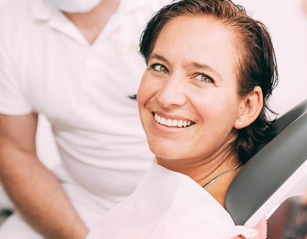 Eine Patientin mit strahlend weißen Zähnen lächelt zufrieden nach ihrer Bleaching Behandlung in der Zahnarztpraxis Dr. Pfitzer in Stuttgart