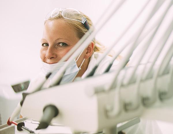 Unsere Mitarbeiterin Daniela Widmer, die im Bereich Patientenbetreuung und Prophylaxe in der Zahnarztpraxis Dr. Pfitzer in Stuttgart arbeitet, lächelt nach einem erfolgreichen Bleaching hinter einem Behandlungsstuhl in die Kamera