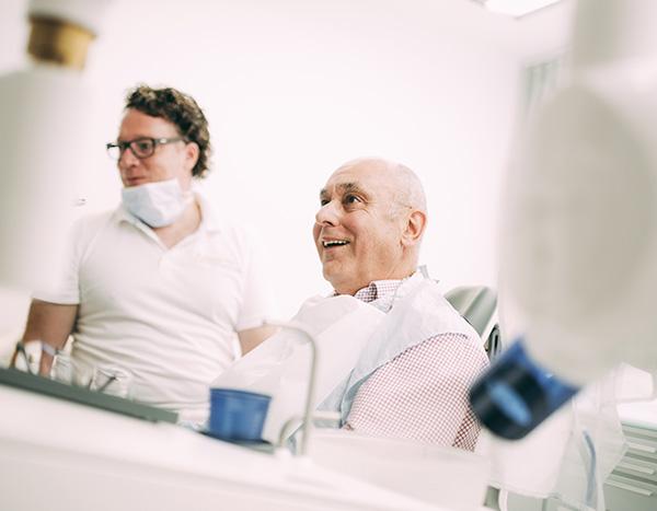 Ein Patient schaut auf dem Behandlungsstuhl gespannt seiner Versorgung mit Zahnimplantaten für feste Zähne entgegen. Im Hintergrund Dr. med. dent. Hanns Joachim Pfitzer, der Implantologe der Zahnarztpraxis Dr. Pfitzer in Stuttgart