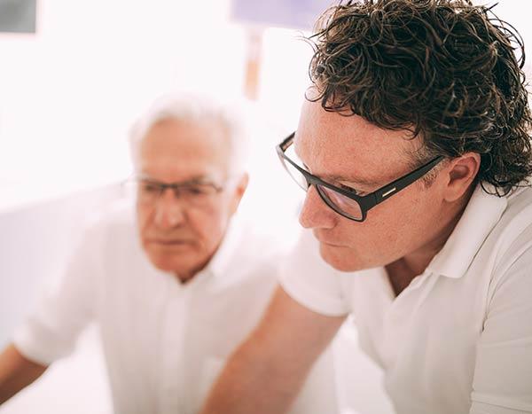 Dr. med. dent. Hanns Joachim Pfitzer forscht mit seinem Vater Dr. med. dent. Hans Pfitzer in seiner Zahnarztpraxis in Stuttgart auf einem nicht näher gezeigten Monitor nach den Ursachen von Kieferschmerzen und den Beschwerden der CMD