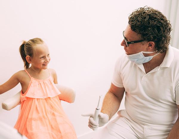 Zahnarzt Dr. med. dent. Hanns Joachim Pfitzer erklärt einer kleiner jungen Patienten in seiner Zahnarztpraxis in Stuttgart-Heumaden mit einer elektrischen Zahnbürste, wie spielerisch ein Zahnarzt-Besuch sein kann