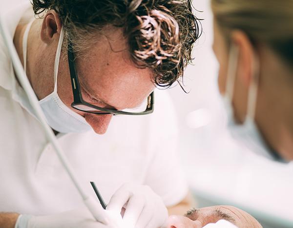 Detailaufnahme von Zahnarzt Dr. med. dent. Hanns Joachim Pfitzer bei einer Parodontitis Behandlung im Rahmen der Prophylaxe und professionellen Zahnreinigung in seiner Zahnarztpraxis in Stuttgart