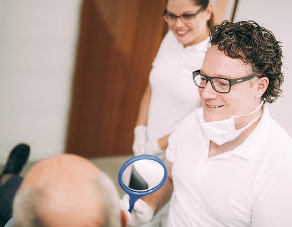 Zahnarzt Dr. med. dent. Hanns Joachim Pfitzer lächelt entspannt einem Patienten vor seiner stressfreien Behandlung in seiner Zahnarztpraxis in Stuttgart zu