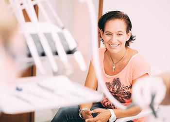 Eine lächelnde Patientin mit schönen natürlichen Zähnen sitzt im Behandlungszimmer und freut sich über das Angebot der Zahnerhaltung in der Zahnarztpraxis Dr. Pfitzer Stuttgart-Heumaden