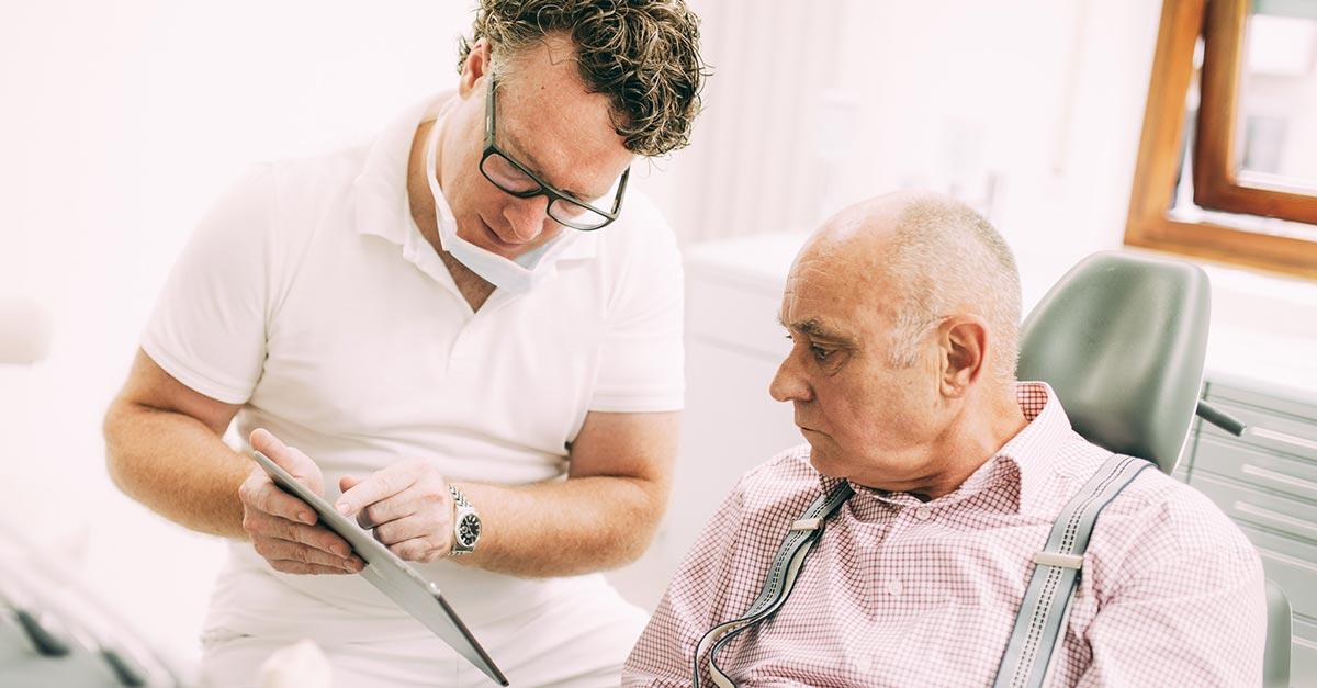 Zahnarzt Dr. med. dent. Hanns Joachim Pfitzer zeigt einem älteren Patienten in seiner Zahnarztpraxis in Stuttgart mit einem Pad das Vorgehen einer Therapie gegen das Schnarchen mit individuellen Schnarchschienen