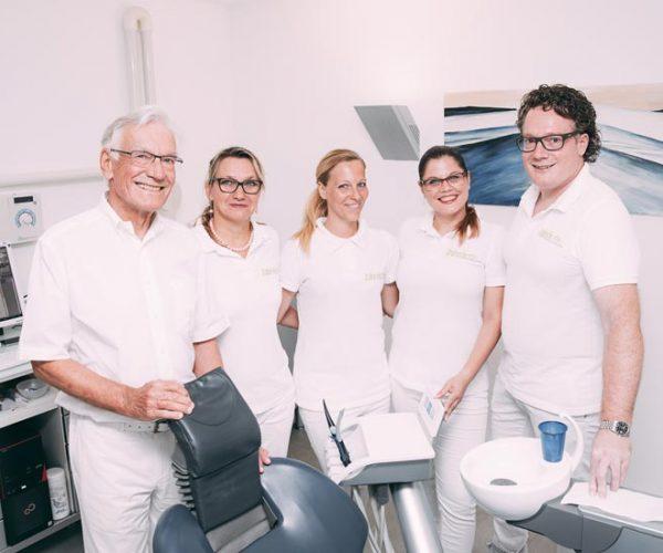 Zahnarzt Dr. med. dent. Hanns Joachim Pfitzer posiert zusammen mit einem Teil seines Praxisteams in einem Behandlungszimmer in der Zahnarztpraxis Dr. Pfitzer in Stuttgart